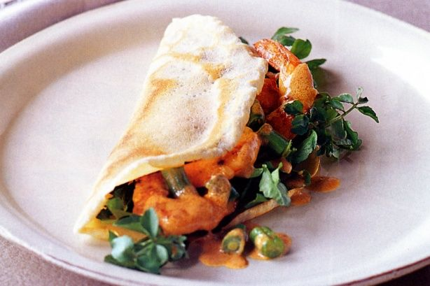 Enfold the light coconut crepe around the spicy curry prawns and enjoy. Don't forget to keep some crepe to mop up the sauce.