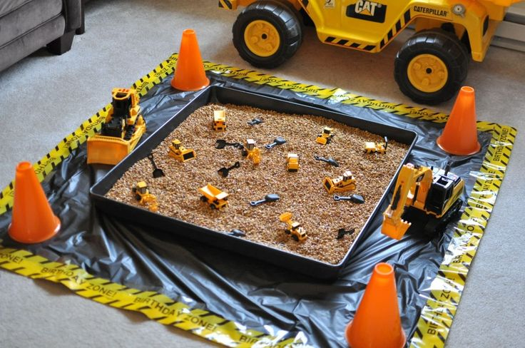 The main party activity was the digging pit. I found the large plastic tray at Tractor Supply and filled it with aquarium rocks. Garrett already had several construction vehicle toys, but I purchased a few more, along with some small plastic shovels for digging. I created the mat underneath using a black plastic tablecloth