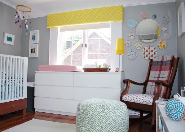 A cômoda branca de seis gavetas também é usada como trocador. Além de uma bandeja de madeira com os itens necessários para a troca de fraldas, a cômoda também foi decorada com uma vibrante luminária amarela.
