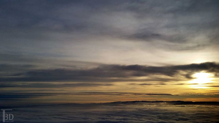 a photo of Mount Diablo from above the clouds at sunrise