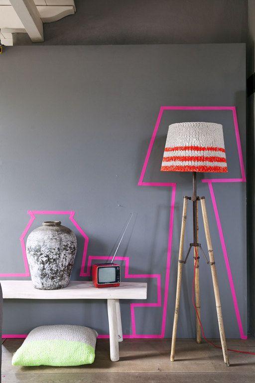 Zo maak je je huis nét even wat spannender: plak langs de contouren van je meubels en accessoires – de lamp, het bankje en de vaas – knalroze tape.