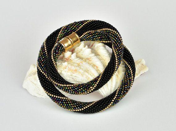 Dies ist eine wunderschöne gehäkelte Perlenkette, hergestellt aus den hochwertigen japanischen Miyuki Rocailles der Größe 11/0. Die verarbeiteten Farben sind schwarz, gold und der Mix arabian nights. Das Armband ist mit einen Magnetverschluß versehen. Der Umfang beträgt 12 Perlen.  Sie können das Armband zu vielen Outfits tragen, da es sportlich und elegant ist.  Die Länge des Armbandes beträgt 45 cm und die Breite 1,1 cm. Andere Größen stelle ich Ihnen gern auf Anfrage her. Die Kette kann…