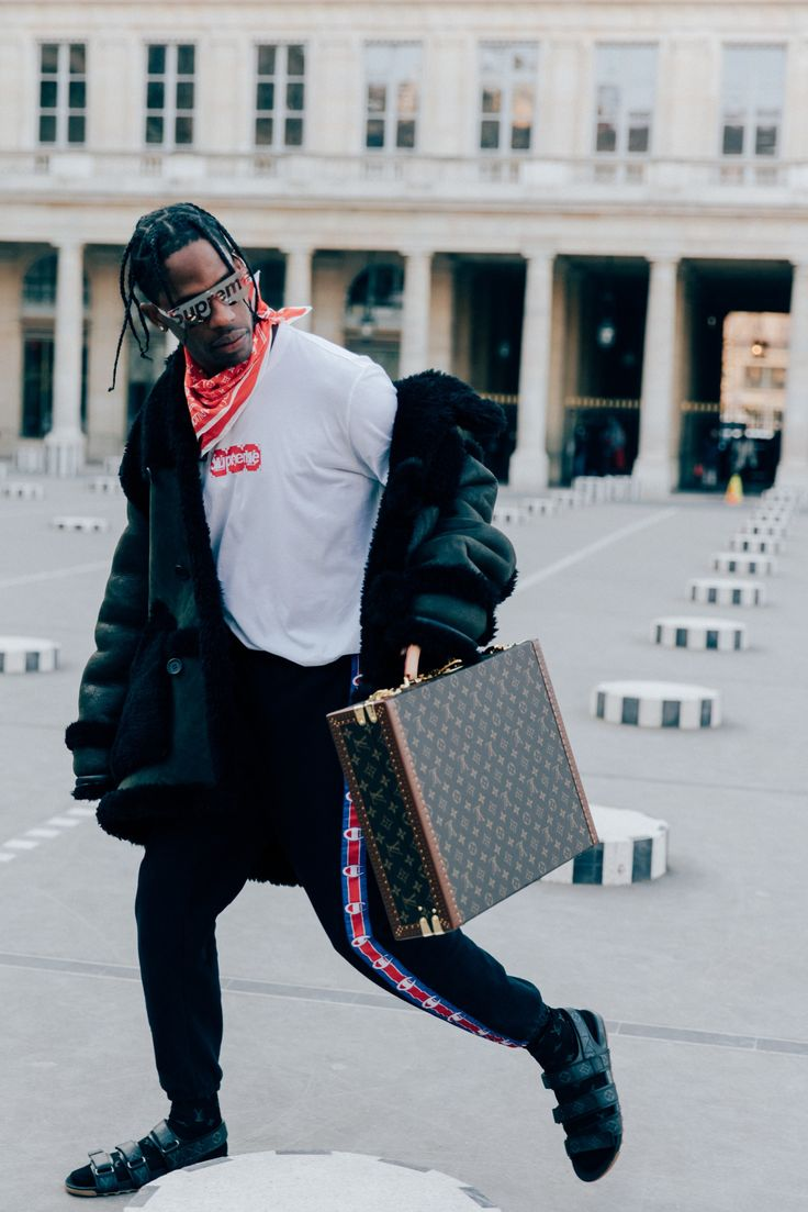 Travis Scott attended the Louis Vuitton Fall/Winter 2017 show during Paris Fashion Week. The Houston rapper was wearing Louis Vuitton sandals, and the new Louis Vuitton x Supreme collaboration t-shirt and sunglasses. Travis Scott also wore a pair of Champion x Vetements sweatpants, Paris, 2017