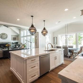 Beautiful kitchen features a pair of black cage lanterns placed above a  white center island topped with white quartzite
