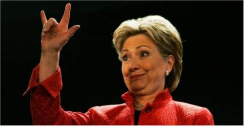"""""""Flashing the horns"""" - iført de satanistiske fargene sort og rødt. Hillary Clinton er Illuminati witch av 5. grad eller høyere. Den okkulte heksa Hillary kalles """"Queen Melusina"""" og benytter Illuminatis okkulte Fugl Fønix symbol. Det hører med til bildet at den lesbiske Illuminati-witchen Hillary gang på gang har artikulert høyrøstet for å starte storkrig - om det så er atomkrig - mot fredsnasjoner som Iran og Russland (sic)..."""