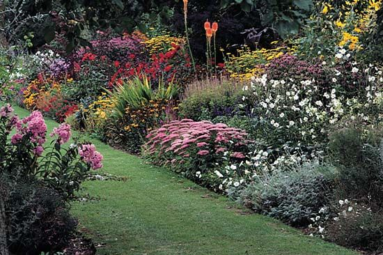 Photograph:Garden phlox, Japanese anemone, horsemint, stonecrop, citronella, red dahlia, sneezeweed, coneflower, aster, and yarrow lend vivid color to this English flower garden.