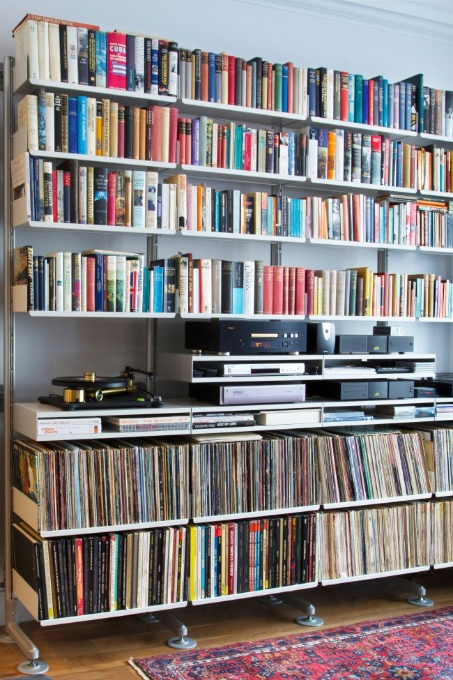 A faithful shelving system bearing its load of books, vinyl and audio equipment. Notice the semi-wall mounted structure with stabilising feet for the heavy load