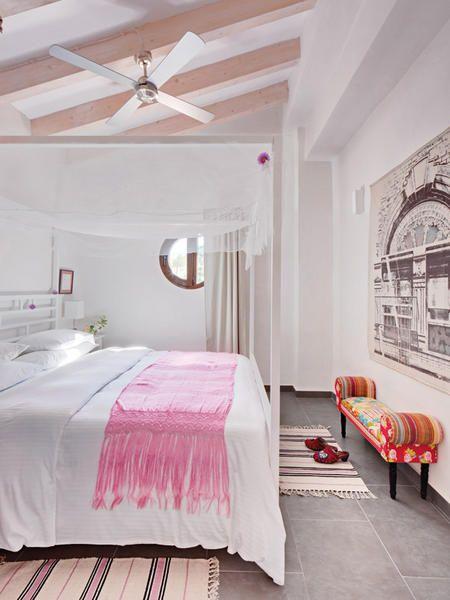 Con ligeros toques de rosa en la vigas del techo, los tapetes, el banco y el rebozo en la cama, se vuelve un dormitorio romántico.