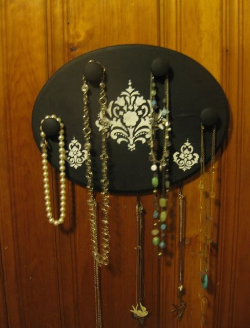 Necklace board/holder.  Regular wooden board from craft store, painted and stenciled, then hot-glued knobs on, and screw some hooks on the bottom!