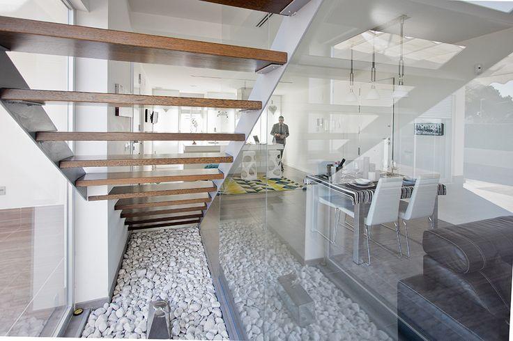 Escalera con peldaños de madera y barandilla de cristal en casa minimalista | Chiralt Arquitectos Valencia.