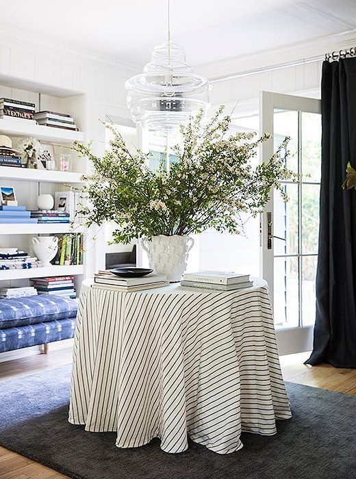 With both front and back doors, Michelle's living room acts as a foyer of sorts. A striped skirted table and modern glass pendant light make the entry extra eye-catching.