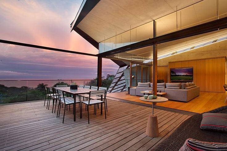Warm Nuance Of Wooden Deck With Outdoor Dining Table Sets Side By Side With The Entertainment Room With Fabric Sectional Sofa