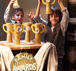 Twee jongens en een meisje houden zelfgemaakte trofeeën in de lucht achter een ad-hocdesk in een hoek van de kamer