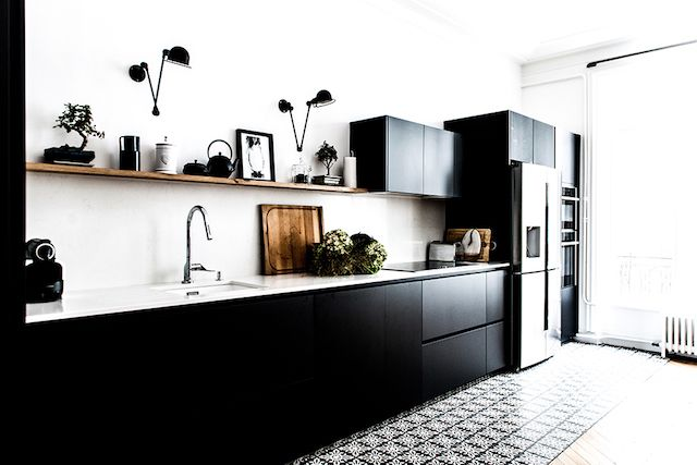 Amazing black kitchen cabinets with white walls and patterned tile floor in French home