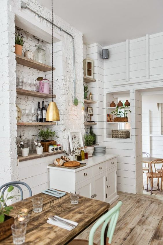 White and light wood kitchen creating a bright and spacious kitchen area. The brass pendant lamp, mint chair and pink watering can add colour and texture to the room