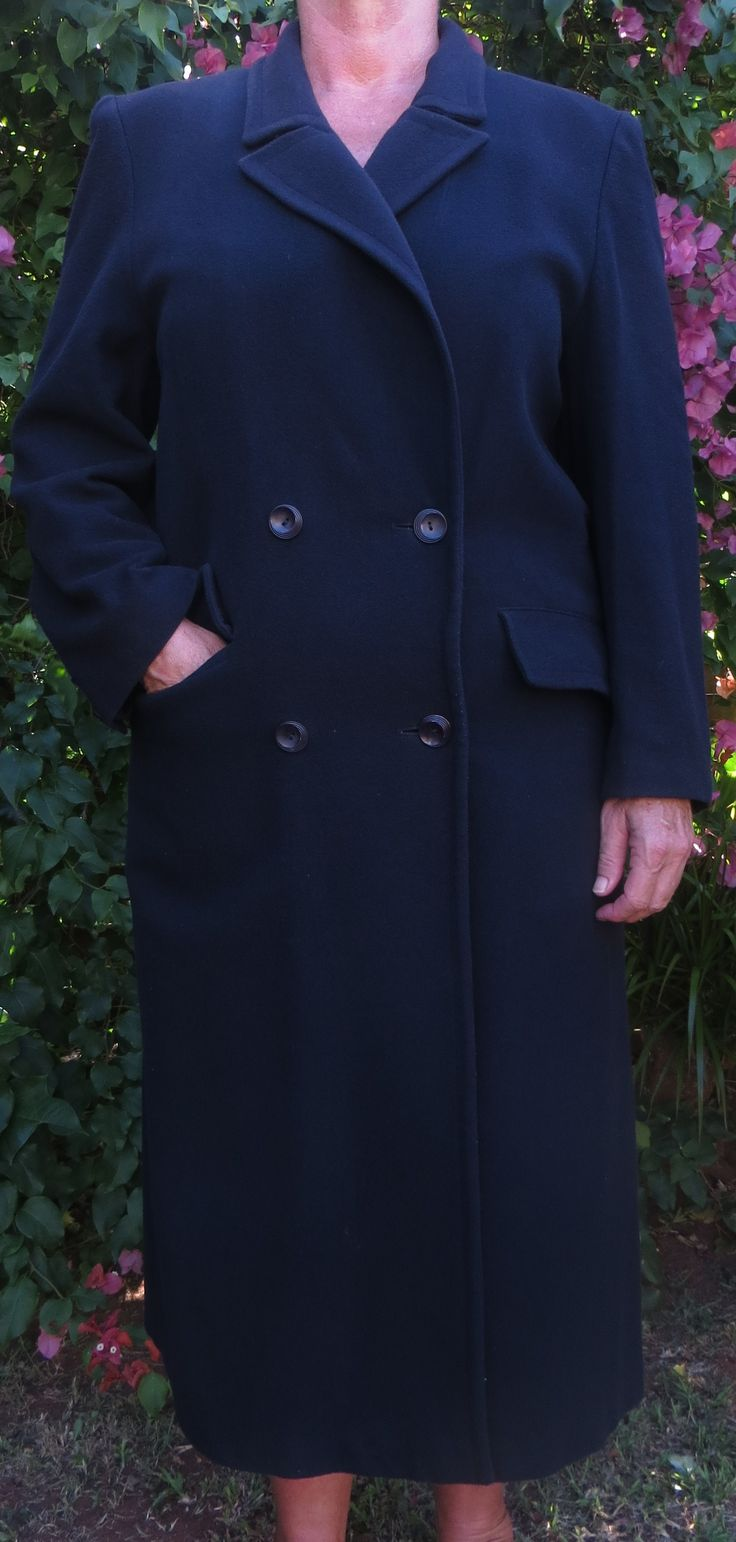 A long navy blue part cashmere, double breasted with two pockets in a straight cut. A light winter wool coat with a full lining, padded shoulders, a back flap and in great condition. Very slight damage to the lining in the back.