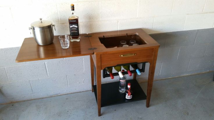 Vintage sewing machine cabinet repurposed as a bar.