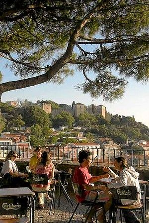"""An open-air cafe at Miradouro da Graca, with Castelo de Sao Jorge in the background, one of the many Terraces with a view in Lisbon. Portugal.""  