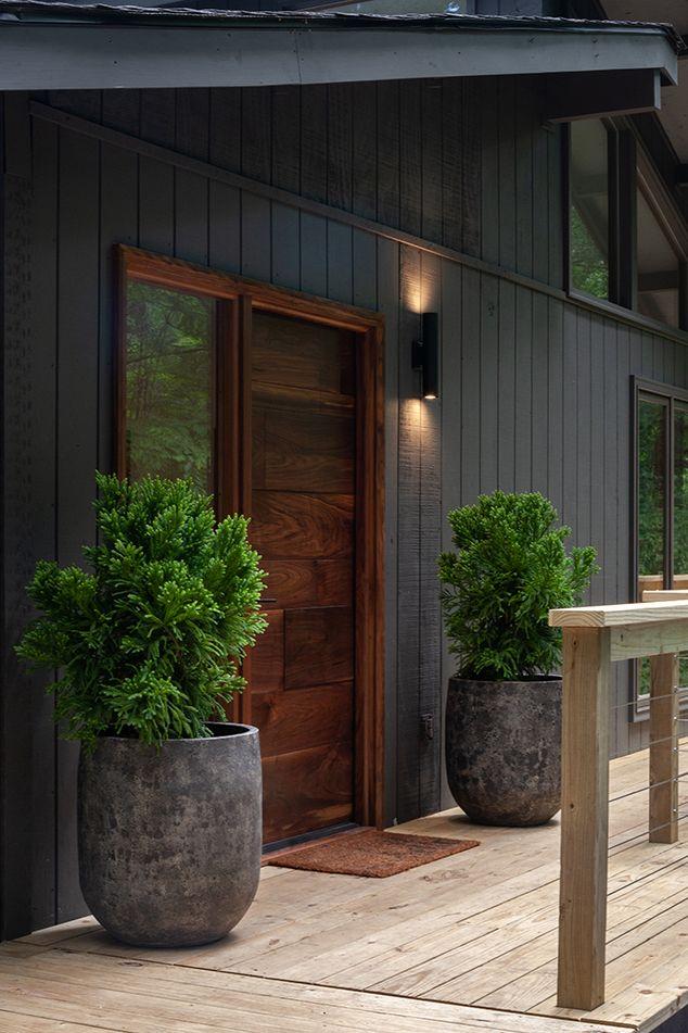 Matte Black Vertical Panel Siding Dark Wood Door Transom Windows Lucy And Company House Paint Exterior Mid Century Exterior Modern Exterior Doors