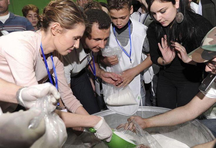 Le président syrien, Bachar Al-Assad (2e G), et son épouse, Asma (G), préparent des colis d'aide humanitaire pour les habitants de Homs (Syrie), le 16 avril 2012, à Damas.