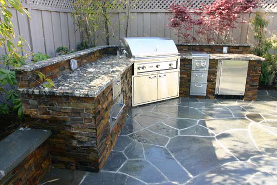 Bbq in corner of outdoor kitchen stacked stone garden for Outdoor stone kitchen designs