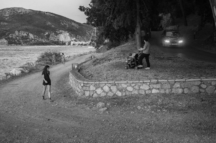 People walking at an esplanade while a car is coming down a hill. A photo taken shortly after sunset as I was preparing to leave the area.