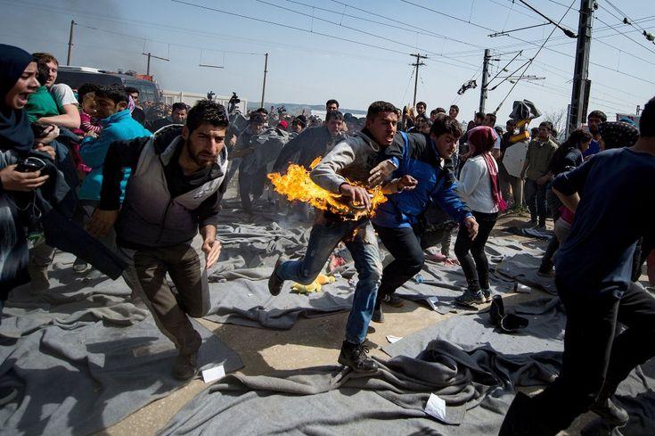Un hombre corre desesperado después de haberse prendido fuego en el campamento griego de Idomeni durante una protesta del grupo de migrantes que mantiene ocupadas las vías del tren para exigir la apertura de las fronteras, el 22 de marzo de 2016.