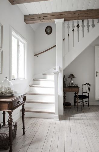 Gorgeous paired-down white hallway with a traditional and echoes of Gustavian Sweden.