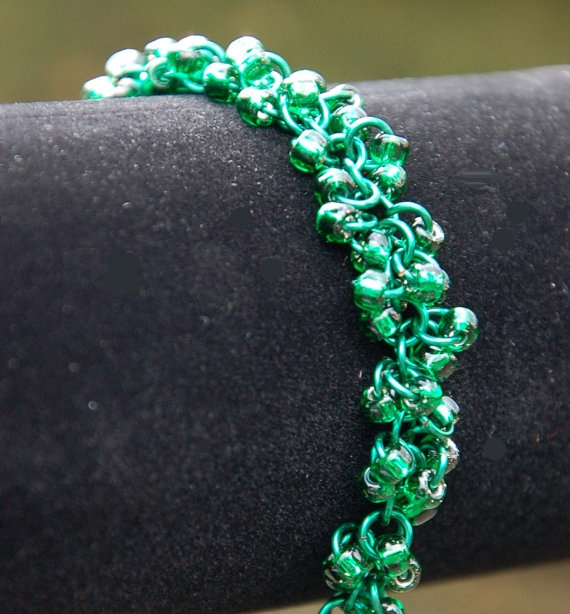 Emerald green chainmaille bracelet. The glass seed beads hang like charms in this delicate weave.