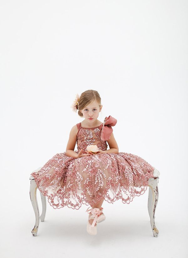 """Doloris Petunia's couture flower girl dresses are fit for a princess! Available in rose, mint, or white, the """"Katy"""" dress is marked by intricate hand beading, a delicate scalloped hemline, and a fun pop-up shoulder bow. 