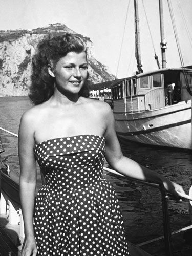 Rita Hayworth In a strapless polka-dot number on a yacht in Capri, 1950.