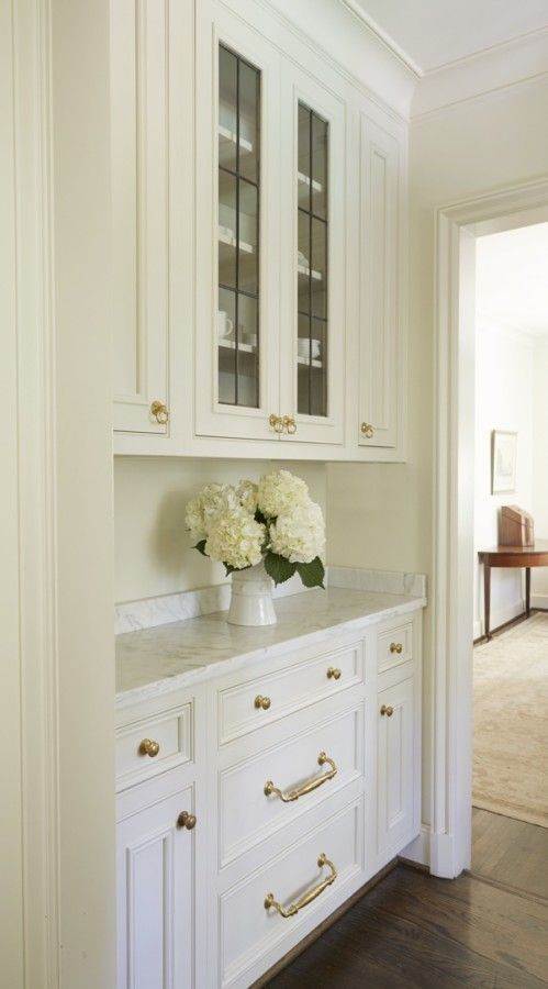 The butler's pantry, between the kitchen and dining room, features the kitchen's Alabama white marble and the simple English white cabinetry with leaded glass doors to make the crystal easily accessible. Cyndy kept the transitional space clean and simple, because they did not in any way want compete with the beautiful dining room furnishings.