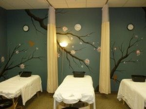 cherry blossom-inspired mural across the massage therapy room walls.