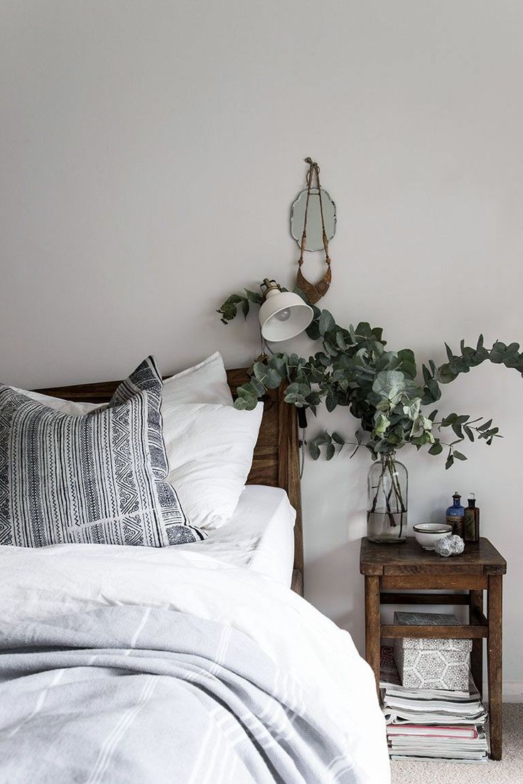 Soothing mix of gray, white and wood in the bedroom, with an arrangement of fresh cut silver dollar eucalyptus.