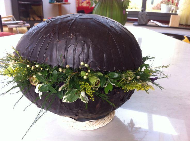 Het piepschuim ei met cacao en kaarsvet villen met oase en volsteken met buxus, viooltjes en kleine bloemetjes