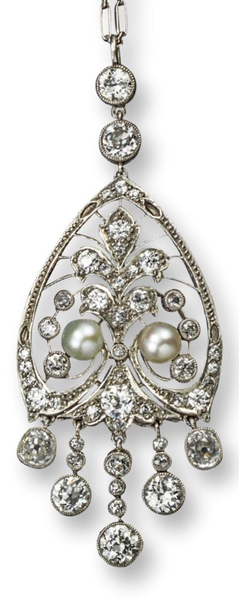 An Edwardian diamond and pearl set pendant, the shield-shaped pendant is centred with a stylised fleurs-de-lys design and is set overall with graduated circular-cut diamonds in platinum. Suspended from two larger circular-cut diamonds and with five articulated diamond pendants. On a fine-link platinum chain. 6cm high.