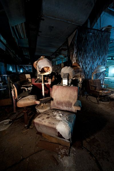 """Beautiful Decay""    Grossinger's Catskill Resort Hotel  Catskill Mountains in Liberty, New York.    Daylight from the large window in the pool's deep end seeps into the basement where beauty parlor chairs sit empty in the former beauty shop."