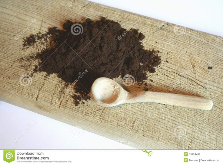 Grounded coffee and a spoon on a brown desk