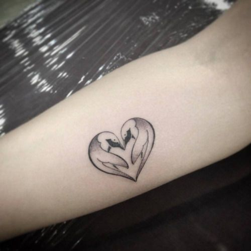 Inner arm tattoo of two pinguins with the shape of a heart by...