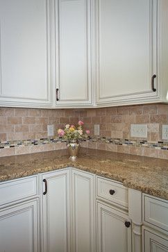 Doors and drawers of this kitchen feature a slow-close element with the drawers also being full extension. The corner base cabinet in this photo houses a lazy susan style trash and recycle center. The back splash is a mix of neutral colored, natural stone broken up by a glass mosaic. All of which are highly popular kitchen elements in the Triangle.