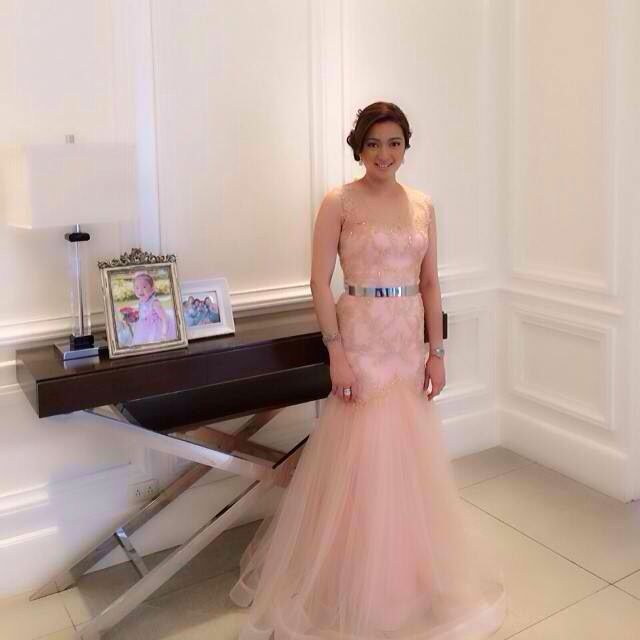 che in a light peach tulle gown with metallic belt.