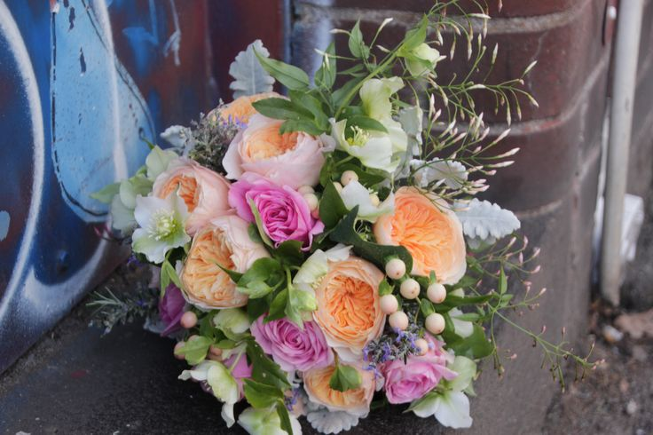 A bright winter bouquet featuring roses, jasmine, hellebores and hypericum berry