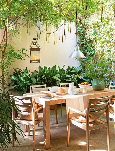 Patio interior con plantas colgantes farolillo y mesa con for Sillas colgantes interior