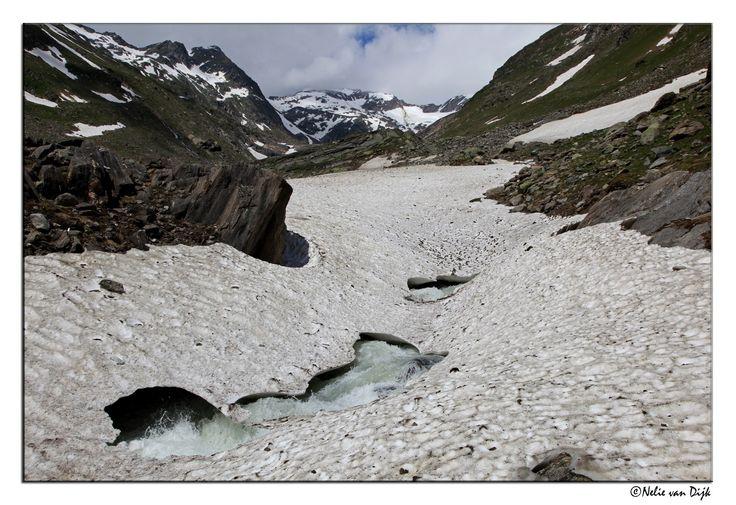 Vreten.  Het ijzige smeltwater vreet zich een weg naar beneden onder de sneeuwvelden door.