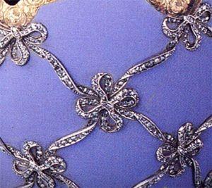 Questo uovo d'oro, è ricoperto di smalto opaco color malva con rifiniture dorate ed è decorato con un traliccio di nastri intrecciati e un fiocco ad ogni intersezione, incrostati di diamanti taglio rosa e con un diamante incastonato a ciascuna delle estremità.