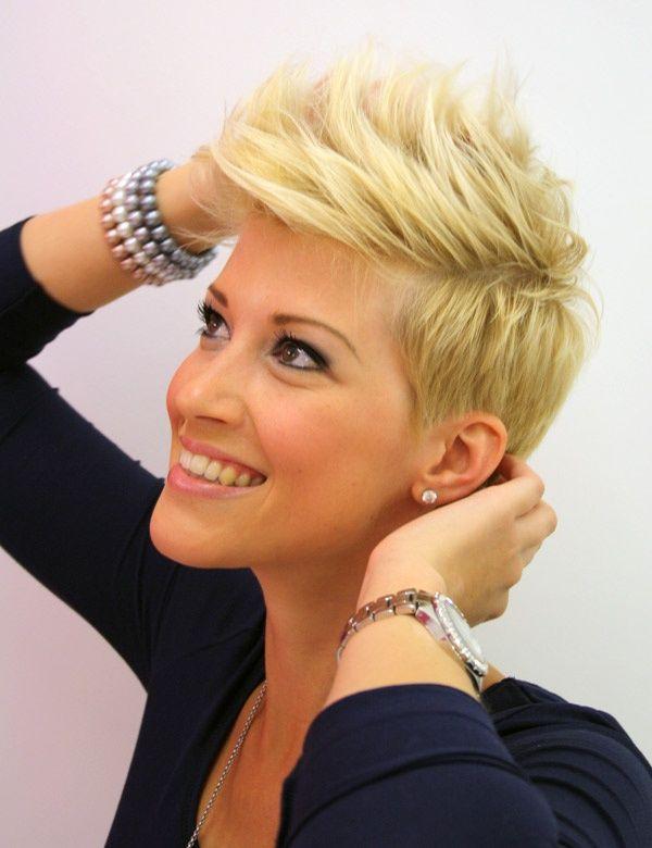 Afin de suivre la tendance, les cheveux de cette jeune femme ont été coupés court, mais gardés plus longs sur le dessus de la tête, ce qui a permis au coiffeur de réaliser une grosse crête. La coloration est blonde, mais on peut remarquer quelques pointes qui ont été colorées en rose.