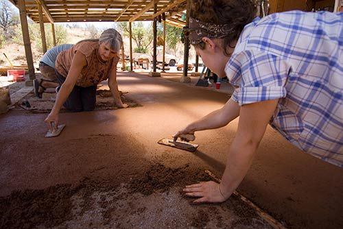 creating an earthen floor (made of clay, sand, and straw,much like earth plaster for the wall) the finished product is very hard, shiny and durable!