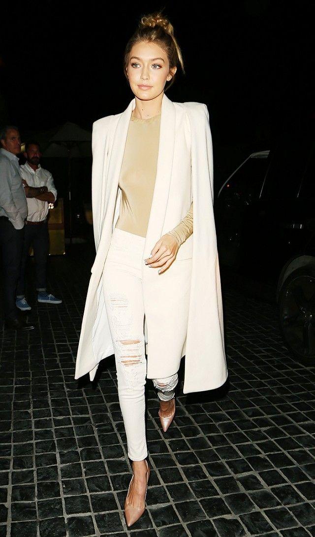 Gigi Hadid looks sleek in a nude top, long white coat, distressed skinny jeans, and nude heels