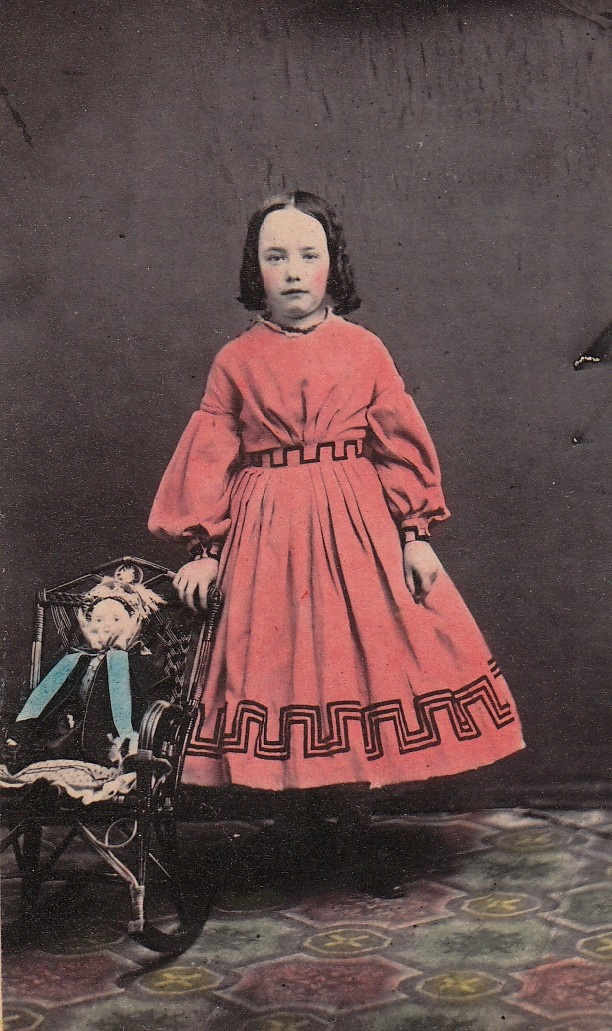 Girl with pink-tinted dress and a doll in a little rocking chair, 1860's