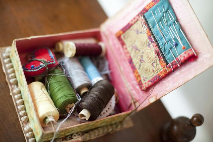 Open sewing box with assorted colored reels of yarn or cotton, pins and needles viewed from above in a handicraft concept - free stock photo from www.freeimages.co.uk